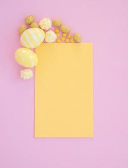 ピンクのテーブルに空白の黄色い紙でイースターエッグ