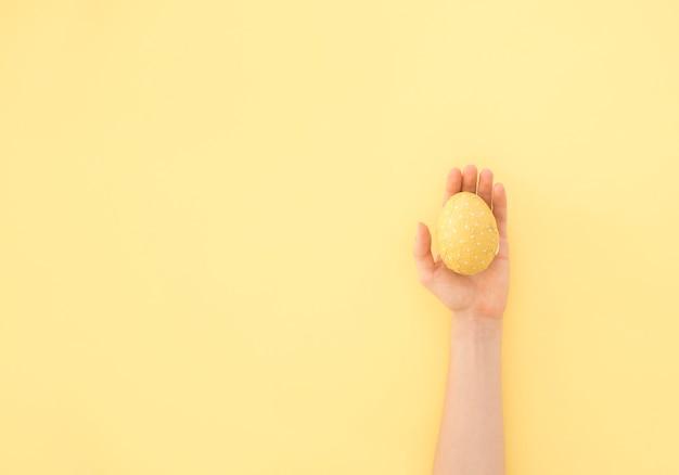 黄色のイースターエッグを手に持っている人