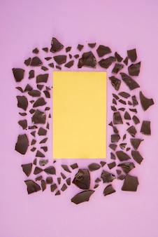 白紙の紙のテーブルの上のひびの入ったチョコレート
