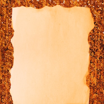 スパンコール織物に対して焼けた紙のクローズアップ