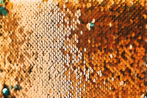 光沢のある金色のスパンコール素材のクローズアップ