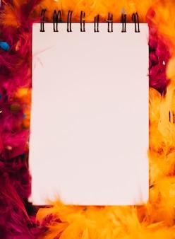 オレンジと赤の羽毛製の襟巻の前にスパイラルメモ帳のクローズアップ