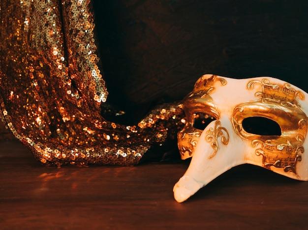 仮面舞踏会マスクと木製の机の上の光沢のある金色のスパンコールテキスタイル