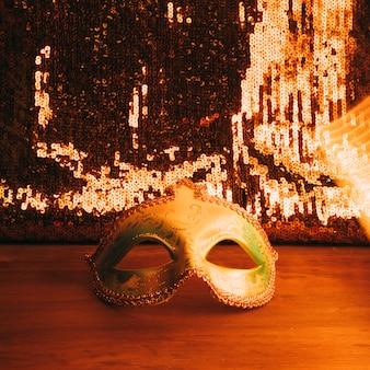 黄金の輝きのスパンコールのついた木製の机の上の緑のカーニバルマスク