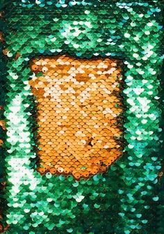 背景として光沢のあるスパンコールのついた黄金と緑の繊維の平面図