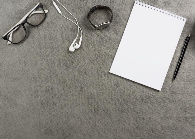 眼鏡の上から見た図。イヤホン腕時計。スパイラルメモ帳と灰色の机の上のペン