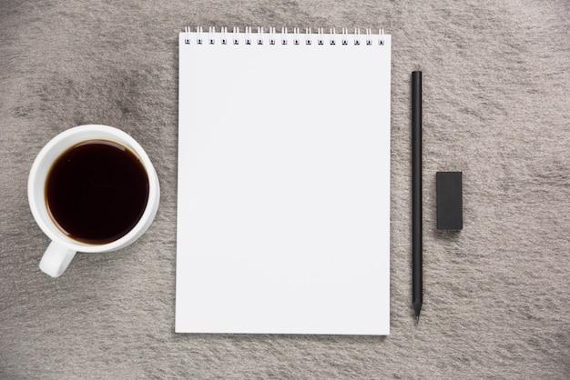 コーヒーカップの上から見た図。黒消しゴムと灰色の机の上の鉛筆で空白のスパイラルメモ帳