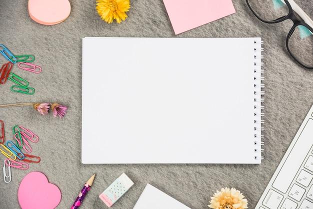 灰色の背景に事務用品に囲まれた空白のスパイラルメモ帳