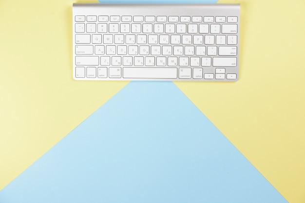 黄色と青の背景にワイヤレスの白いキーボード