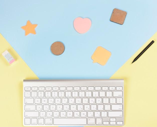 鉛筆でさまざまな種類の図形。消しゴムとキーボードの青と黄色の背景
