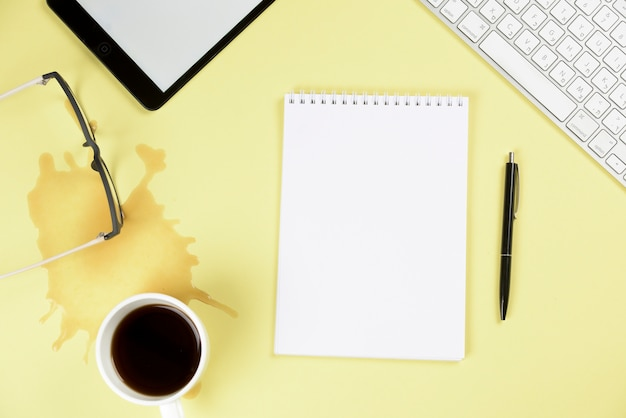 こぼれたコーヒー。めがねデジタルタブレットキーボード;空白のスパイラルメモ帳と黄色の背景にペン