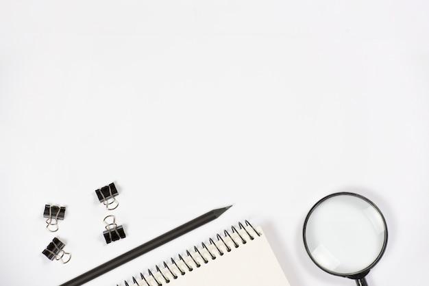 虫眼鏡。鉛筆;白い背景の上のスパイラルメモ帳とブルドッグクリップ