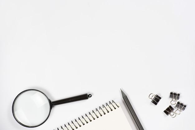 虫眼鏡のクローズアップ。鉛筆;白い背景の上のスパイラルメモ帳とブルドッグクリップ