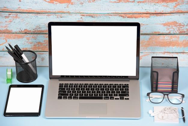 ノートパソコンとデジタルタブレットのオフィスの机の上の白い空白の画面表示