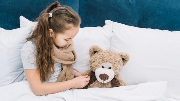 体温計でテディベアの温度をチェックする病気の女の子