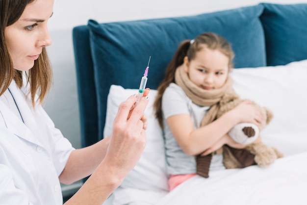 女性医師の手を見て怖い病気の女の子が薬で注射器を充填