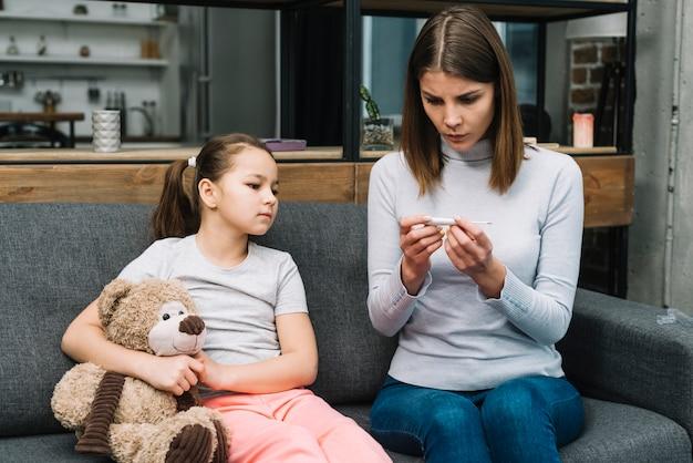 Девушка сидит на сером диване, держа плюшевого мишку, глядя на женщину, проверка температуры на термометре