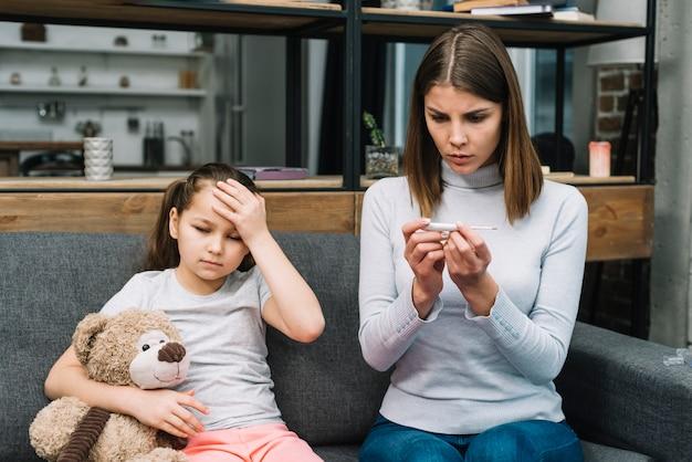 若い女性がテディベアと座っている女の子のそばに座って温度計の温度をチェック
