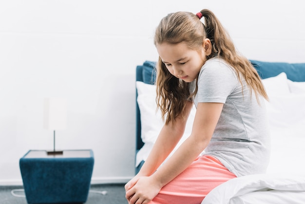 膝の痛みに苦しんでベッドの上に座っている女の子のクローズアップ