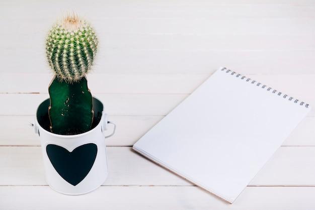 木製の机の上の空白のスパイラルメモ帳の近くのカップのサボテンの植物