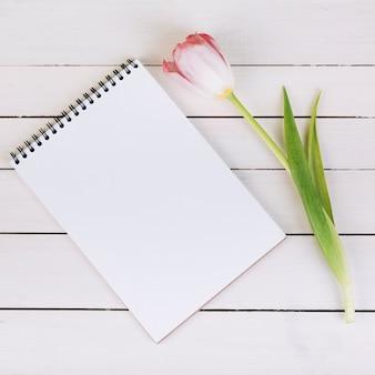 空白の白いスパイラルメモ帳と木製の机の上の新鮮なピンクのチューリップ
