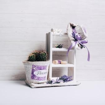机の上の袋の帽子と木製の棚の上のサボテンの鍋