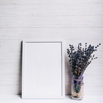木製の背景の白い机の上のラベンダーガラス花瓶の近くの白い空白フレーム