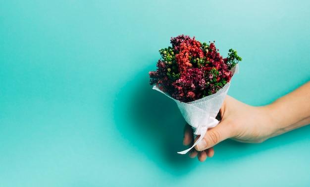 ターコイズブルーの背景に対して装飾的な花の花束を持っている手のクローズアップ