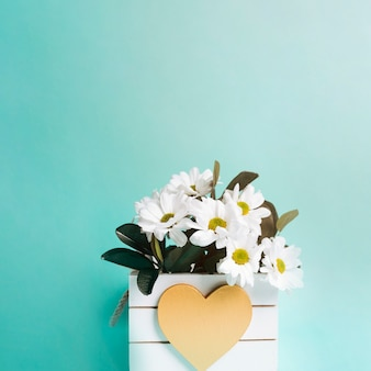 ターコイズブルーの背景にハート形の花瓶