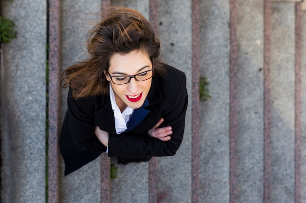 Деловая женщина в костюме стоит на лестнице снаружи