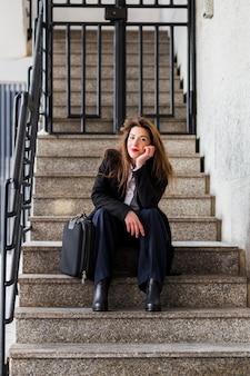 Деловая женщина в черной куртке сидит на лестнице