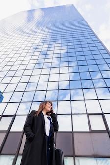 外の電話で話している若いビジネス女性