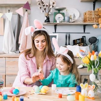 母と娘のテーブルでイースターの卵を塗る