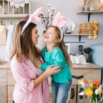 小さな女の子と笑っているバニーの耳の母