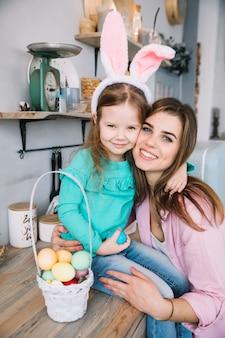 Молодая женщина обнимает дочь в ушах зайчика