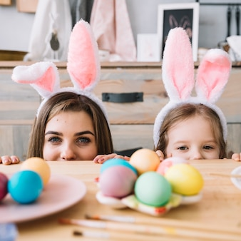 小さな女の子とテーブルの後ろに隠れているバニーの耳の母