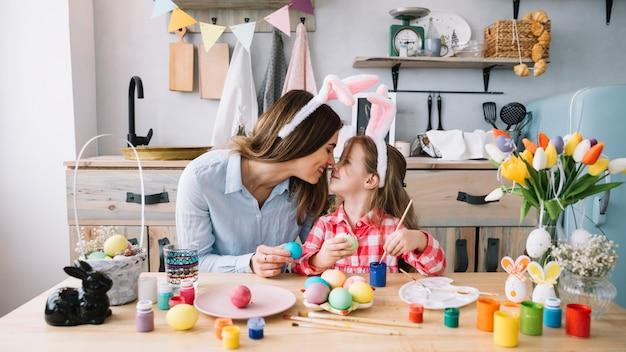女の子と母親のイースターのための卵を描きながら鼻に触れる