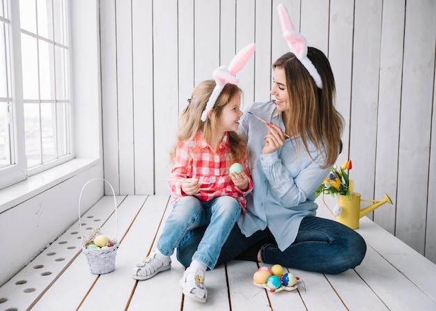 女の子と母親のイースターエッグをペイントしながら楽しんで