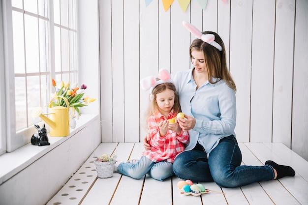 小さな女の子とウサギの耳のイースターの卵を塗る母