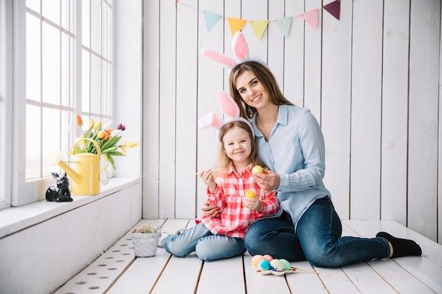 幸せな女の子とイースターの卵を塗るウサギの耳の母