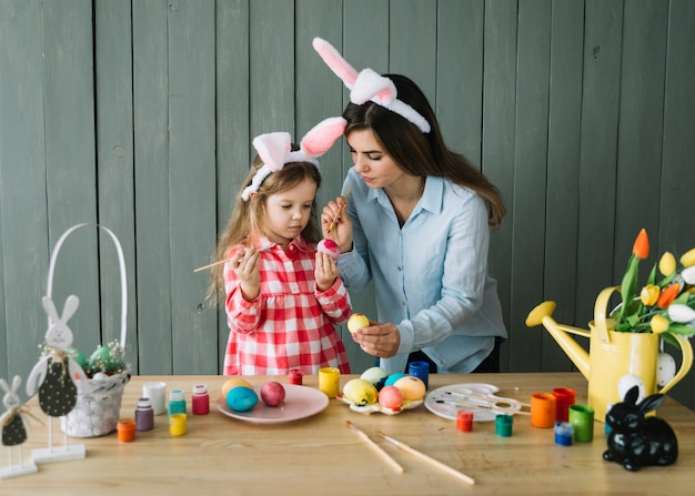 少女と母のイースターの卵を塗るバニーの耳