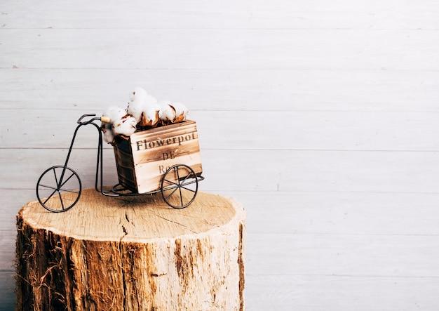 木の切り株の上のアンティーク自転車に白い綿ポッド