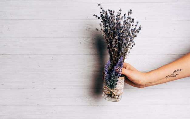 木製の背景に対してラベンダーの花束を持っている人のクローズアップ