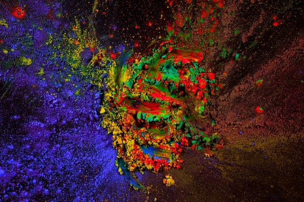 暗い背景上に広がるホーリーカラーパウダーの混合物