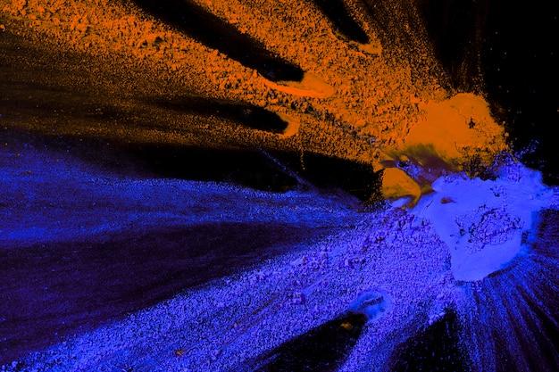 暗い背景に飛び散ったオレンジとブルーのパウダーカラーのオーバーヘッドビュー
