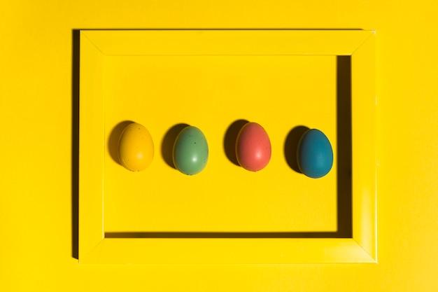 黄色のテーブルの上のフレームのイースターエッグ