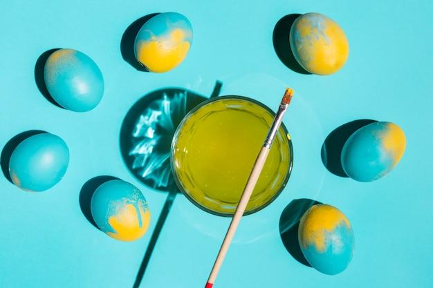 Красочные пасхальные яйца с кистью и стаканом воды на столе