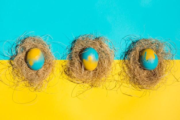 明るいテーブルの上の巣のイースターエッグ