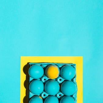 青いテーブルの上のフレームのラックにカラフルなイースターエッグ