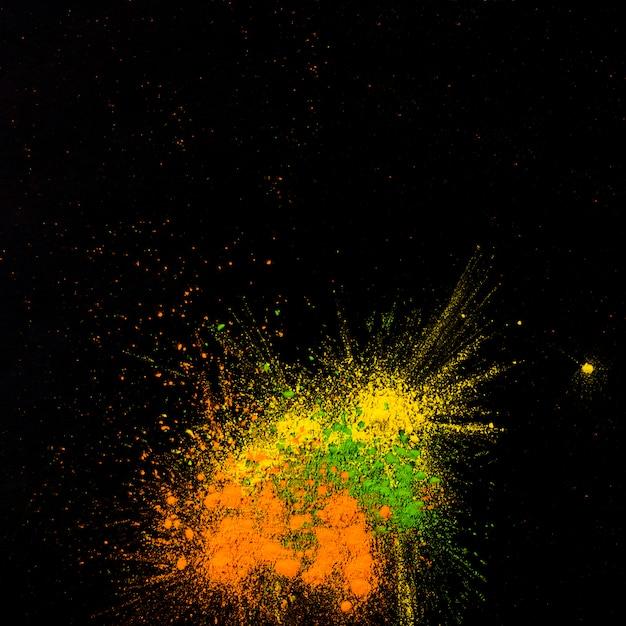 黄色、緑、オレンジ色の粉体が黒い背景に飛び散った